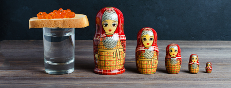 Sandwiches with red caviar of salmon fish. A glass of vodka, matryoshka. The concept of Russian tradition.