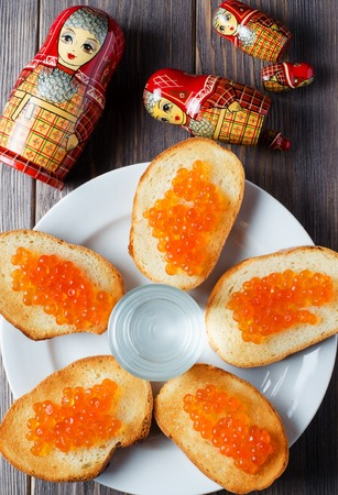 Sandwiches with red caviar of salmon fish. A glass of vodka, matryoshka. The concept of Russian tradition. Flat Lay. Vertical photo Banco de Imagens