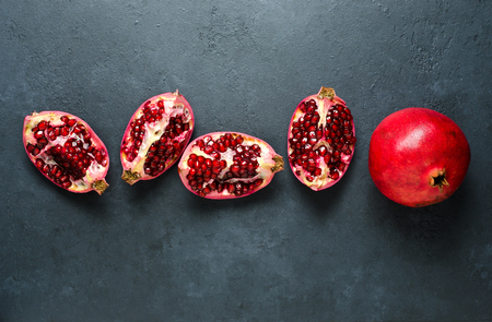 Broken and whole pomegranate fruit. Dark background. Flat top view. Copy space