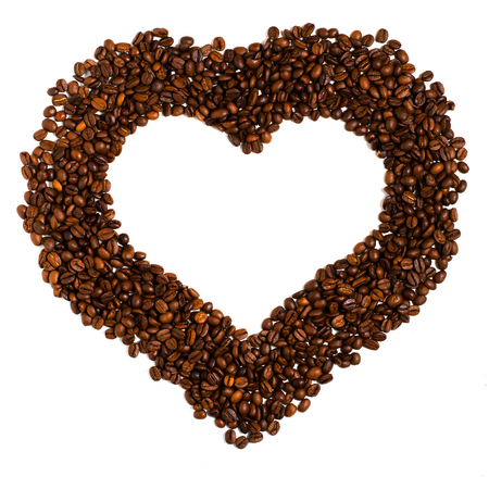 Roasted coffee beans on white background. Space for text in the shape of a heart. The concept - a love for coffee Banco de Imagens