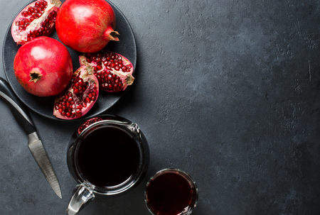 Broken and whole pomegranate fruit. Juice in a glass decanter. Dark background. Flat top view. Copy space