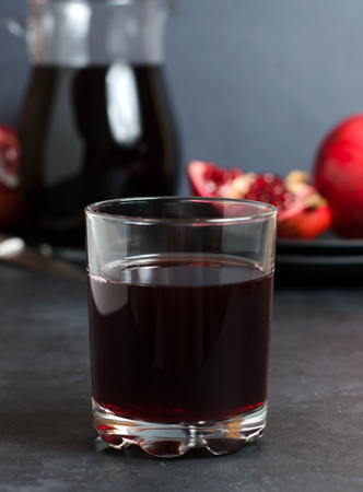 Pomegranate, pomegranate juice in a glass Cup. Dark background. Side view. The concept of therapeutic nutrition Banco de Imagens