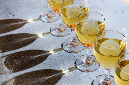 White wine in glass glasses. Blue background. Dark shadows from glasses