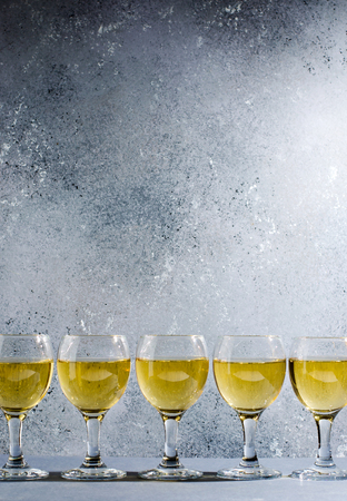White wine in glass wine glasses. Blue background. Copy space