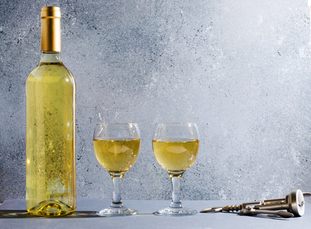 White wine in glass wine glasses, a bottle of wine, corkscrew. Blue background. Copy space