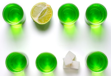 Absinthe green liquor in glasses. Alcoholic hallucinogenic beverage. White background. Pieces of lime and white sugar. Copy space. Flat lay Banco de Imagens