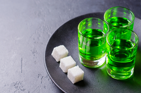 Absinthe green liquor in glasses. Alcoholic hallucinogenic beverage. Dark background. Pieces of white sugarin a plate . Copy space Banco de Imagens