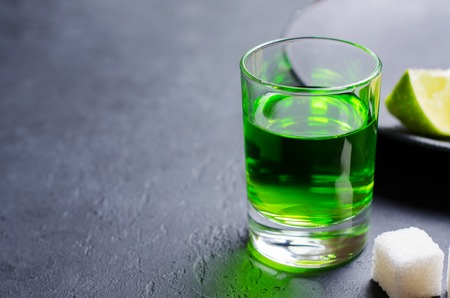 Absinthe green liquor in glasses. Alcoholic hallucinogenic beverage. Dark background. Pieces of lime and white sugar. Copy space Banco de Imagens