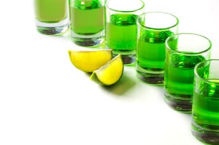 Absinthe green liquor in glasses. Alcoholic hallucinogenic beverage. White background. Pieces of lime. Copy space Banco de Imagens