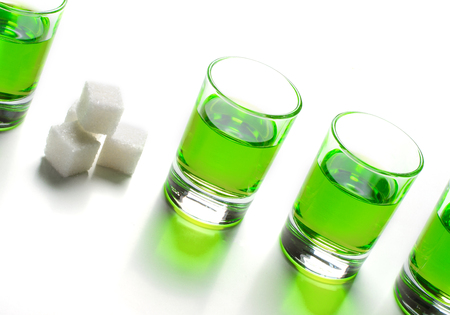 Absinthe green liquor in glasses. Alcoholic hallucinogenic beverage. White background. Pieces of white sugar. Copy space Banco de Imagens
