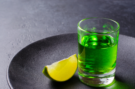 Absinthe green liquor in glasses. Alcoholic hallucinogenic beverage. Dark background. Pieces of limein a plate. Copy space Banco de Imagens