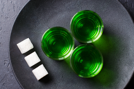 Absinthe green liquor in glasses. Alcoholic hallucinogenic beverage. Dark background. Pieces of white sugar in a plate