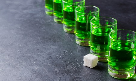 Absinthe green liquor in glasses. Alcoholic hallucinogenic beverage. Dark background. Pieces of white sugar. Copy space