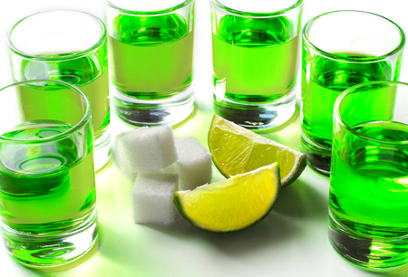 Absinthe green liquor in glasses. Alcoholic hallucinogenic beverage. White background. Pieces of lime and white sugar.