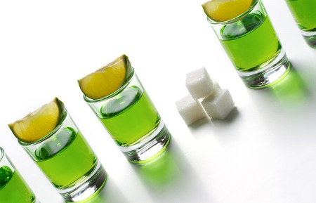 Absinthe green liquor in glasses. Alcoholic hallucinogenic beverage. White background. Pieces of lime and white sugar. Copy space Banco de Imagens