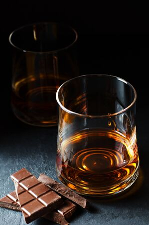 Cognac or rum or Bourbon in a glass. Pieces of chocolate. Alcohol tasting. Dark background