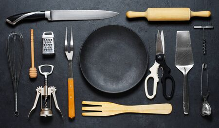 Wooden and metal kitchen utensils and a black plate . Tools for cooking. Dark background. Flat lay