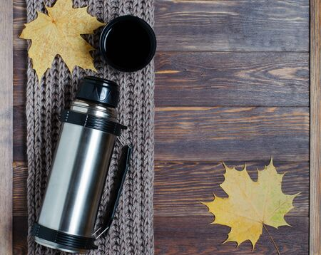 Metal , hot tea or coffee in a mug. Brown knitted scarf, maple leaf. Autumn mood. Copy space. Brown wooden background
