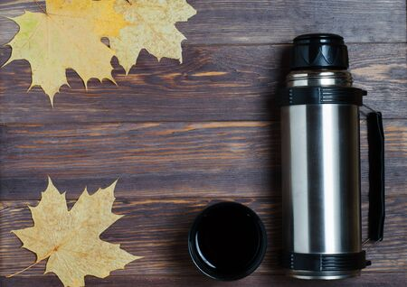 Metal , hot tea or coffee in a mug. Maple leaf. Autumn mood. Brown wooden background. Copy space