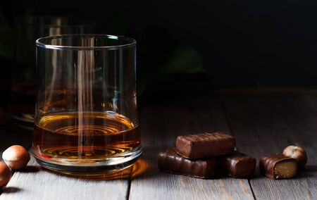 Cognac or whisky or brandy in a glass. Pieces of chocolate and hazelnuts. Dark background. Copy space