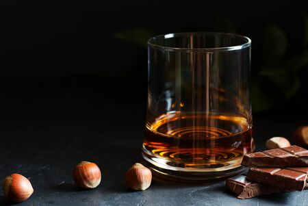 Cognac or rum or Bourbon in a glass. Pieces of chocolate and hazelnuts. Dark background. Copy space