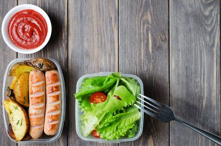 Grilled sausages, potatoes, green lettuce with tomatoes in a plastic box. Unhealthy diet. Wooden background. Copy space.