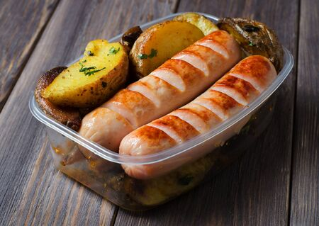 Grilled sausages and potatoes in a plastic box. Unhealthy diet. Wooden background