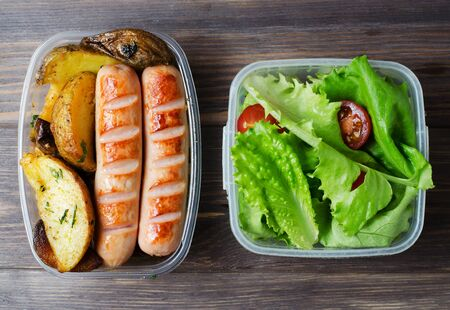 Grilled sausages, potatoes, green lettuce with tomatoes in a plastic box. Unhealthy diet. Wooden background 写真素材