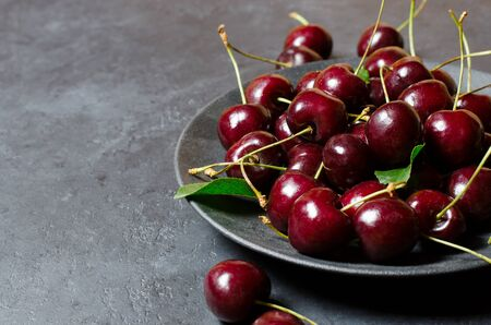Lots of ripe cherries on a black plate. Dark background, copy space