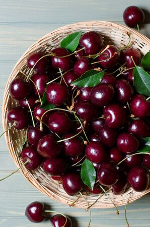 Lots of ripe red cherries in a wicker basket. Light wooden background. Flat lay