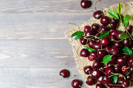 Cherries on the old fabric. Fresh crop. Rustic style. Wooden background. Flat lay, copy space 写真素材