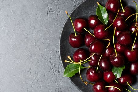 Lots of ripe cherries on a black plate. Dark background. Flat lay, copy space