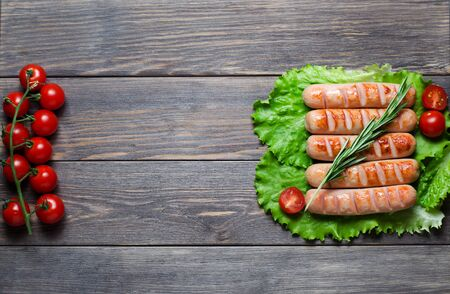 Grilled sausages on green lettuce leaves, rosemary, red cherry tomatoes on a branch. Wooden dark background. Copy space