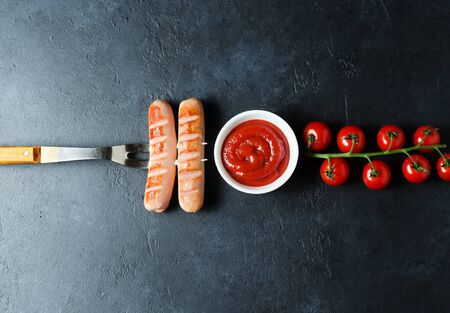 Grilled sausages fried on a metal fork. Unhealthy diet. Ketchup, cherry tomatoes. Dark background. Copy space 写真素材