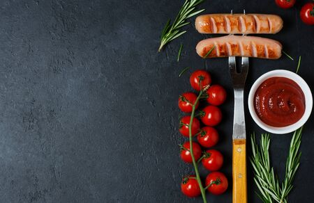 Grilled sausages fried on a metal fork. Ketchup, cherry tomatoes, rosemary. Unhealthy diet. Dark background. Copy space