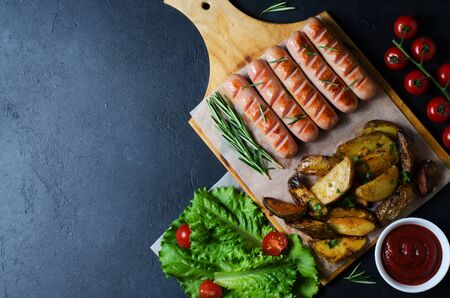 Grilled sausages on a wooden chopping Board. Fried potatoes, rosemary, tomatoes, green lettuce leaves, tomato ketchup. Unhealthy diet. Dark background. Copy space