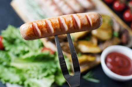 Grilled sausages on a wooden chopping Board. Fried potatoes, rosemary, tomatoes, green lettuce leaves, tomato ketchup. Unhealthy diet.