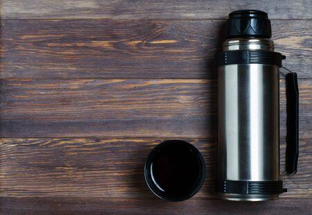 Metal , hot tea or coffee in a mug. Autumn mood. Brown wooden background 写真素材
