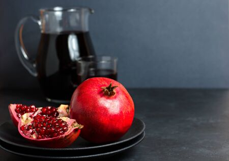Pomegranate, pomegranate juice in a glass Cup. Dark background. Side view. Copy space 스톡 콘텐츠