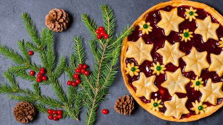 Christmas home sweet cake with jam on dark background. Green branches of a Christmas tree 写真素材