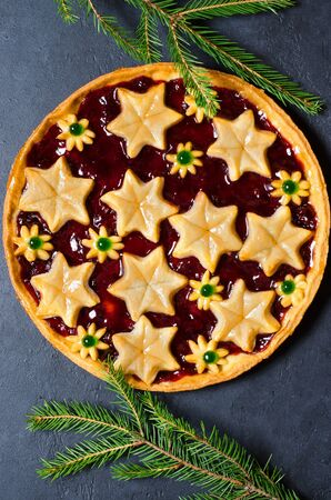 Christmas home sweet cake with jam on dark background. Green branches of a Christmas tree. Vertical photo