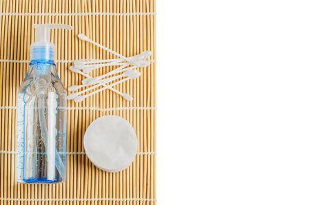 Women's makeup remover accessories. Gel in a transparent bottle, cotton buds, cotton pads. Copy space.
