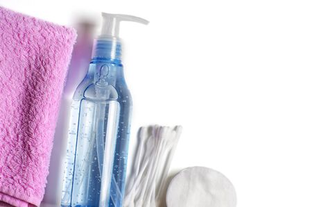 Womens makeup remover accessories. Gel in a transparent bottle, cotton buds, cotton pads, pink towel