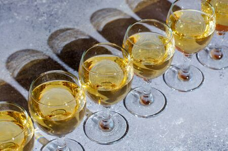 White wine in glass glasses. Blue background. Dark shadows from glasses.