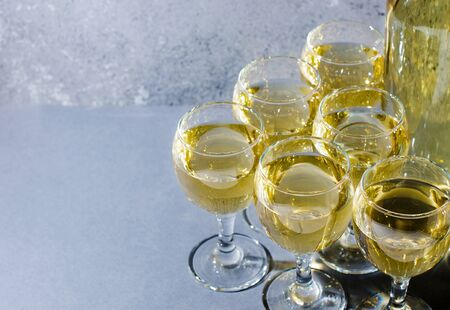 White wine in glass wine glasses, a bottle of wine. Blue background. Copy space. 写真素材