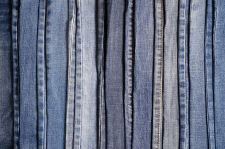 Denim. Blue jeans background. Stack of blue jeans different shadows.