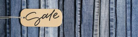 Denim. Blue jeans background. Sale - handwritten inscription on a paper label