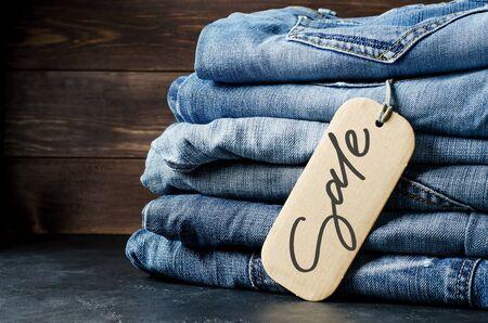 Denim. Lots of blue jeans on wooden background. Sale - handwritten inscription on a paper label 写真素材