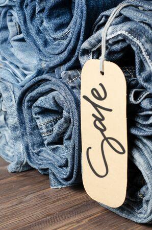 Denim. Lots of blue jeans rolled up. Sale - handwritten inscription on a paper label