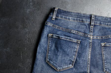 Denim. Blue jeans on black background